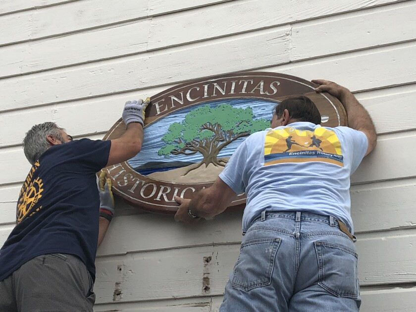 Rotarians hung a refurbished sign at the schoolhouse, which serves as the home of the Encinitas Historical Society.