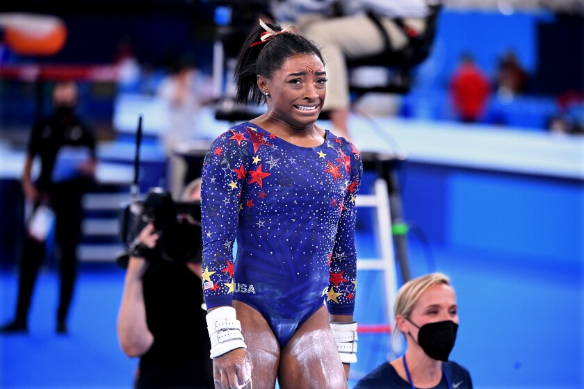 U.S. gymnast Simone Biles reacts after competing on the uneven bars during team qualifying.