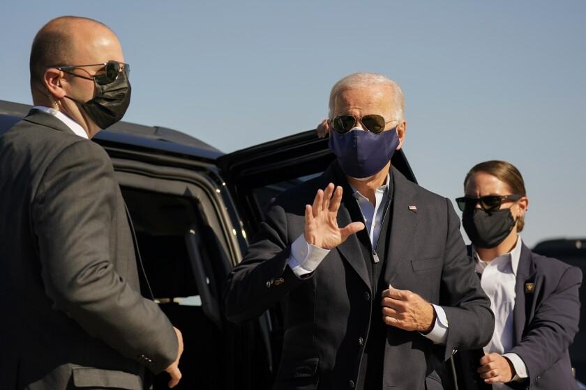 Joe Biden stands outside an SUV