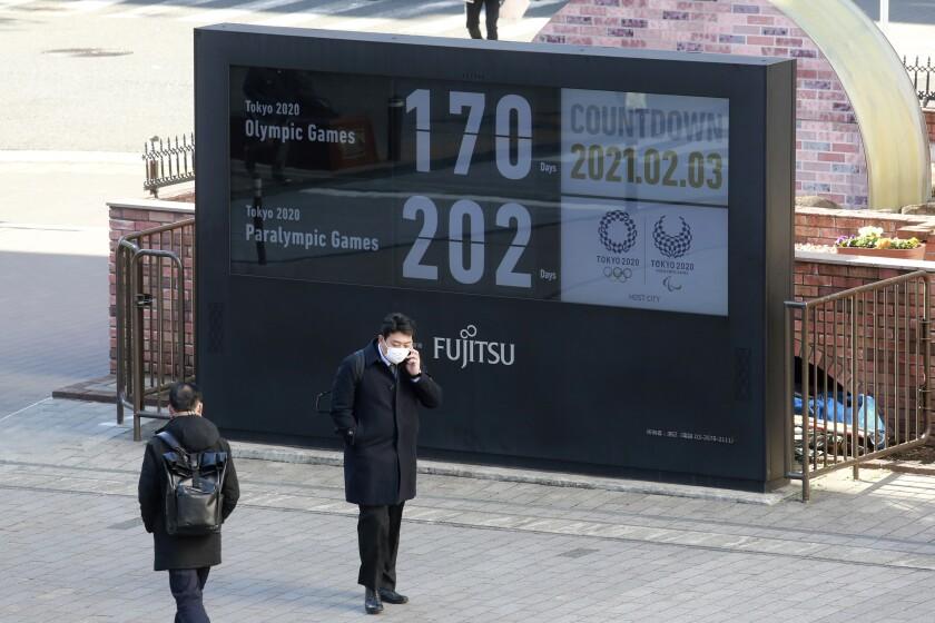 Un individuo frente al reloj con la cuenta regresiva de los Juegos Olímpicos de Tokio