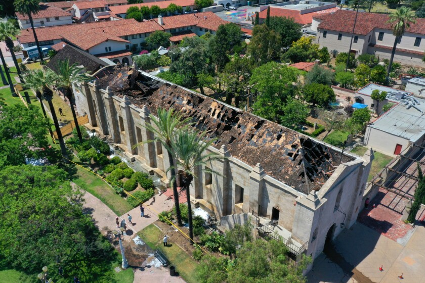 An aerial view shows extensive fire damage to the roof of the San Gabriel Mission Church