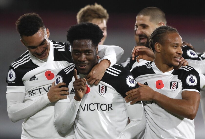 Fulham's Ola Aina, centre, celebrates after scoring his side's second goal during the English Premier League soccer match between Fulham and West Bromwich Albion at Craven Cottage in London, England, Monday, Nov. 2, 2020. (AP Photo/Frank Augstein, Pool)