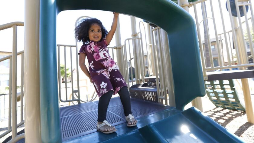 Maipele Burns, 4, prepares to go down the slide, while playing in the park across the street from her home in Camarillo. Maipele was diagnosed at age 2 with acute flaccid myelitis, causing permanent paralysis in her right arm.