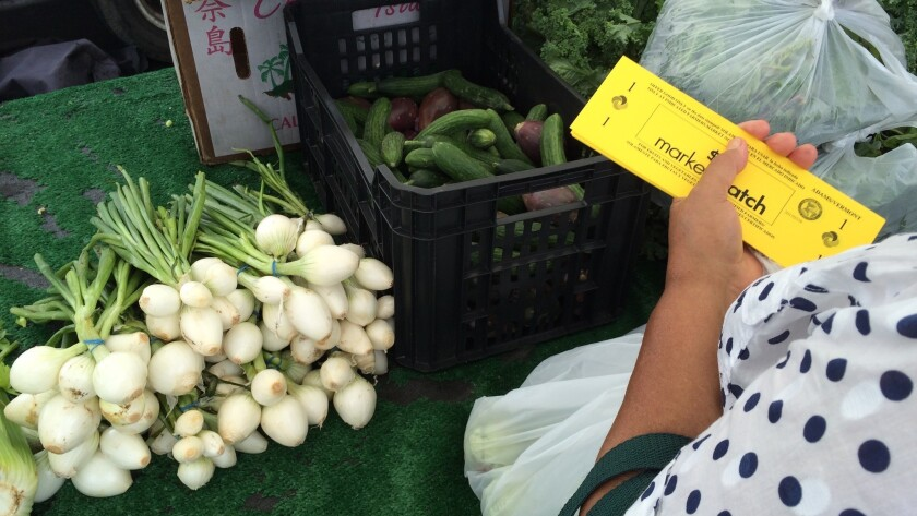 A shopper pays for fresh produce with Market Match at the Adams-Vermont market.