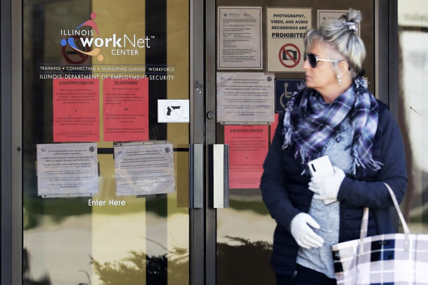 A woman looks to get information about a job application in front of an Illinois Department of Employment Security WorkNet center in Arlington Heights, Ill., last month.