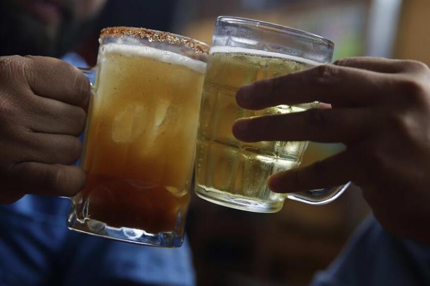 Dos hombres brindan con cerveza el 1 de febrero de 2019, horas previas al inicio de la Ley Seca. El Salvador vivió dicho viernes el segundo día de reflexión para las elecciones presidenciales. EFE/Archivo