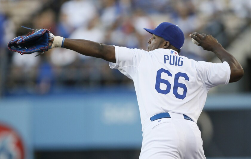 Dodgers right fielder Yasiel Puig fires a ball in after catching a fly ball in foul territory against the Brewers.
