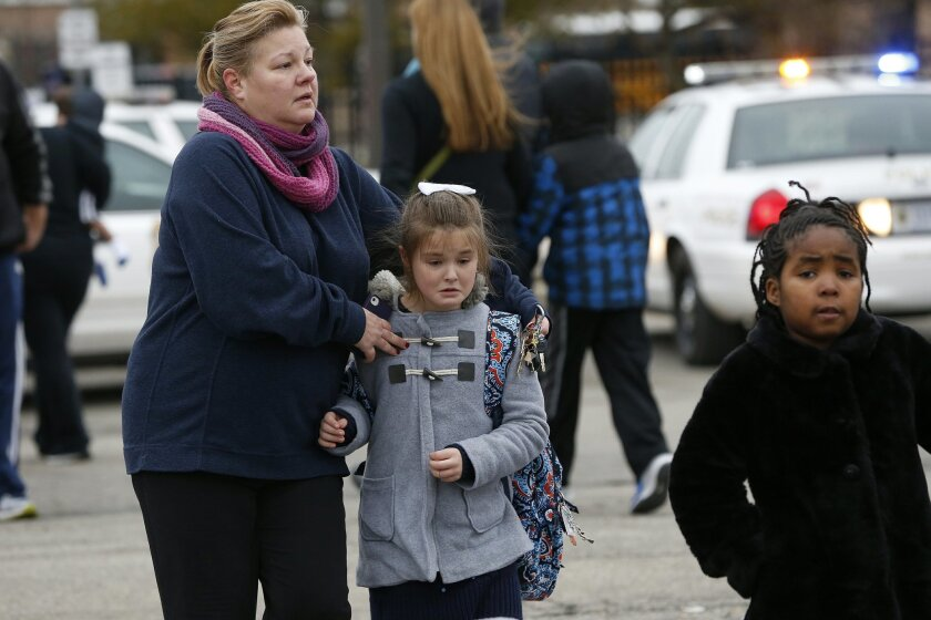 Students at Amy Beverland Elementary School are picked up after school after a bus accident in Indianapolis on Tuesday, Jan. 26, 2016. Authorities said an adult was killed and two children were seriously injured when a bus waiting outside the elementary school suddenly lurched forward and struck them. (Mykal McEldowney/The Indianapolis Star via AP) MANDATORY CREDIT