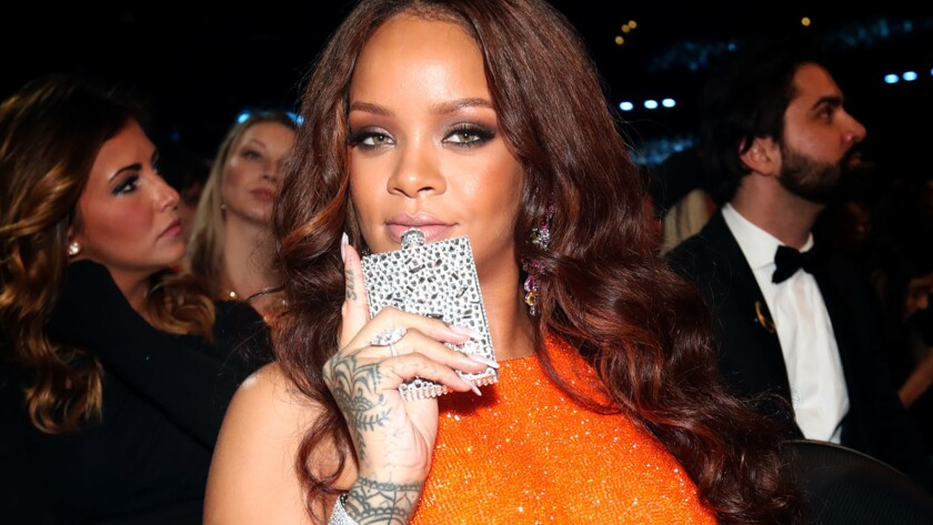 Rihanna, bejeweled flask in hand, strikes a pose for a party photographer.