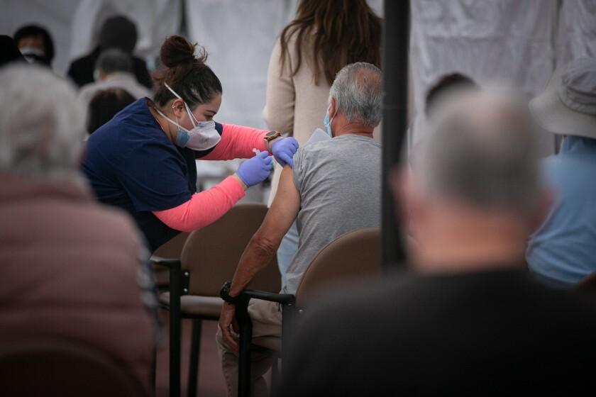 A nurse administers the COVID-19 vaccine