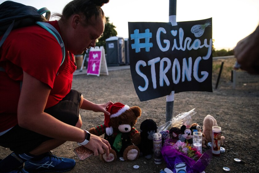 Laura Miller places stuffed bear at memorial to Gilroy Garlic Festival shooting victims