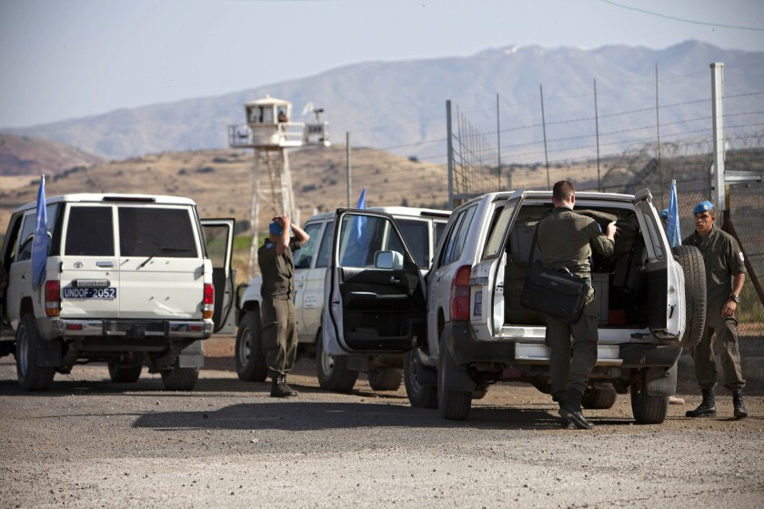 U.N. peacekeepers from Austria carry their belongings at the Quneitra crossing as they begin withdrawing from the Golan Heights.