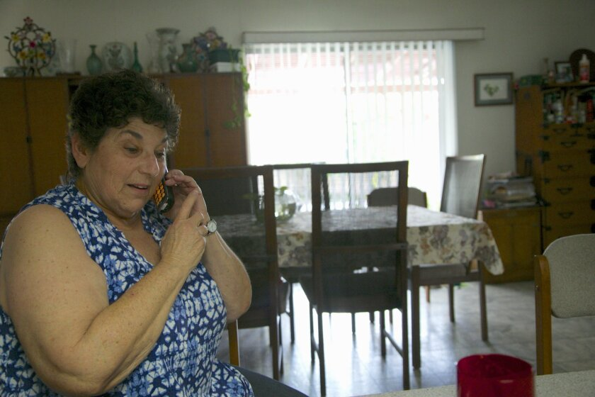 Jeri Vargas takes a phone call at her mother's home in Sherman Oaks in April. Vargas' mother gets several recorded phone calls a day.