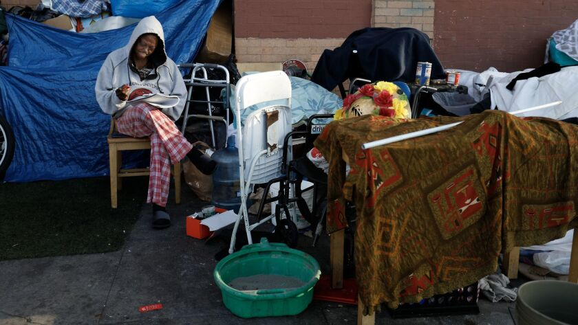 A woman writes in her journal on 5th street in the skid row area of Los Angeles.