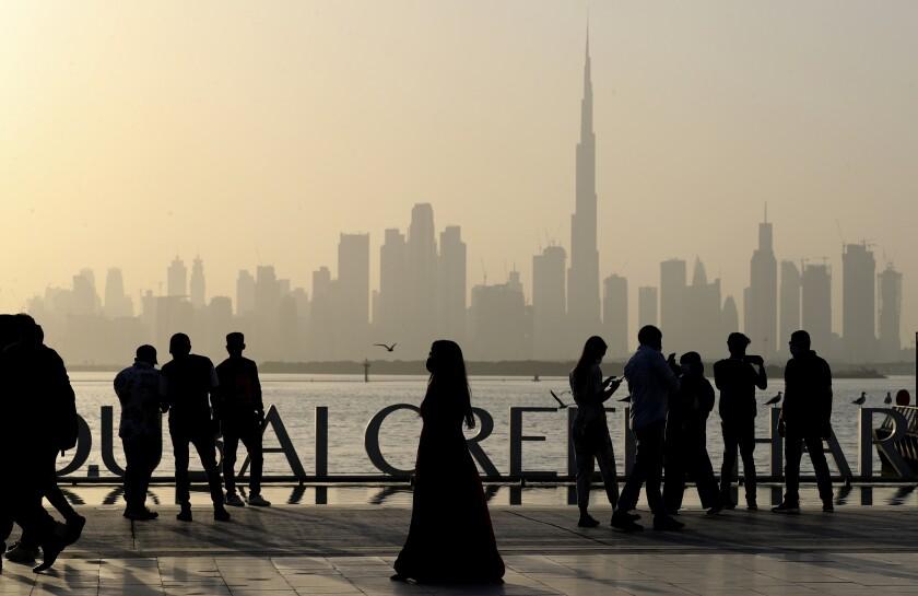 People enjoy their weekend with the view of city skyline and the world tallest tower, Burj Khalifa, in Dubai, United Arab Emirates, Friday, Jan.29, 2021. (AP Photo/Kamran Jebreili)