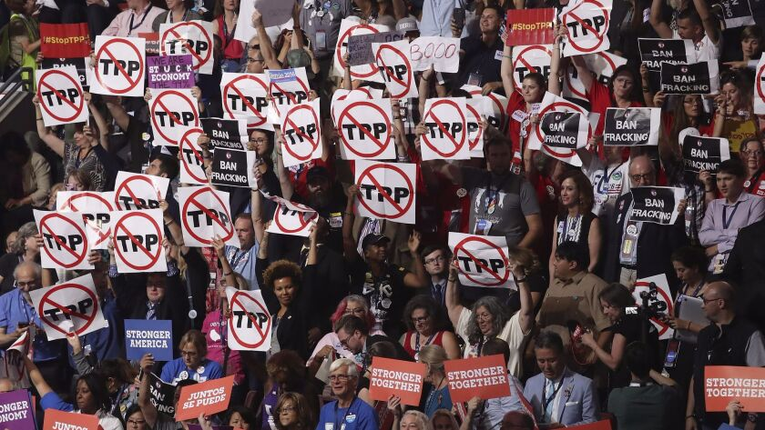 Protesting delegates hold signs that refer to the Trans-Pacific Partnership, during vice presidential candidate Tim Kaine's speech at the Democratic National Convention in July.