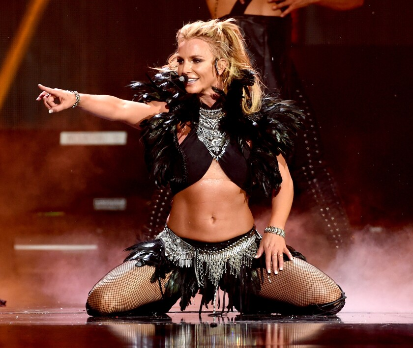 Britney Spears points while sitting on stage.