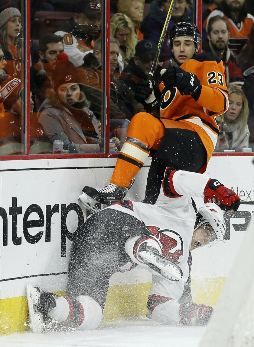 New Jersey Devils' Joseph Blandisi, bottom, and Philadelphia Flyers' Brandon Manning collide during the first period of an NHL hockey game, Saturday, Feb. 13, 2016, in Philadelphia. (AP Photo/Matt Slocum)