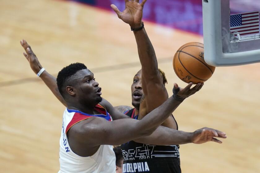 Zion Williamson, alero de los Pelicans de Nueva Orleáns, encesta frente a Dwight Howard, de los 76ers de Filadelfia, el viernes 9 de abril de 2021 (AP Foto/Gerald Herbert)