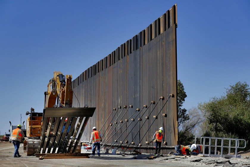 Government contractors erect a section of Pentagon-funded border wall along the Colorado River in Yuma, Ariz.