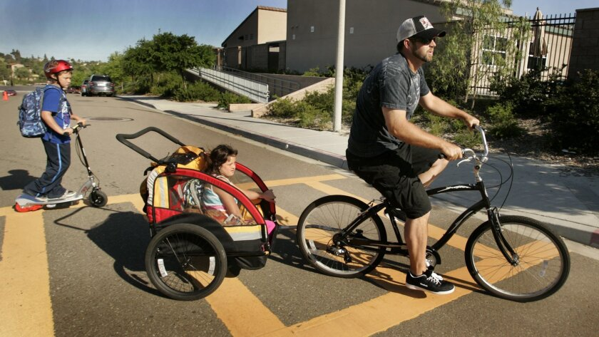 Heath Bell takes daughter Jordyn to school by pulling her in a bicycle trailer, while son Reece follows along on his electric scooter.