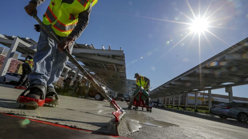 Juan Reyes, left, and Devin Vestal apply a cool pavement material to a parking lot in downtown Los Angeles. City officials hope the pavement will help cool the city and mitigate the effects of climate change.