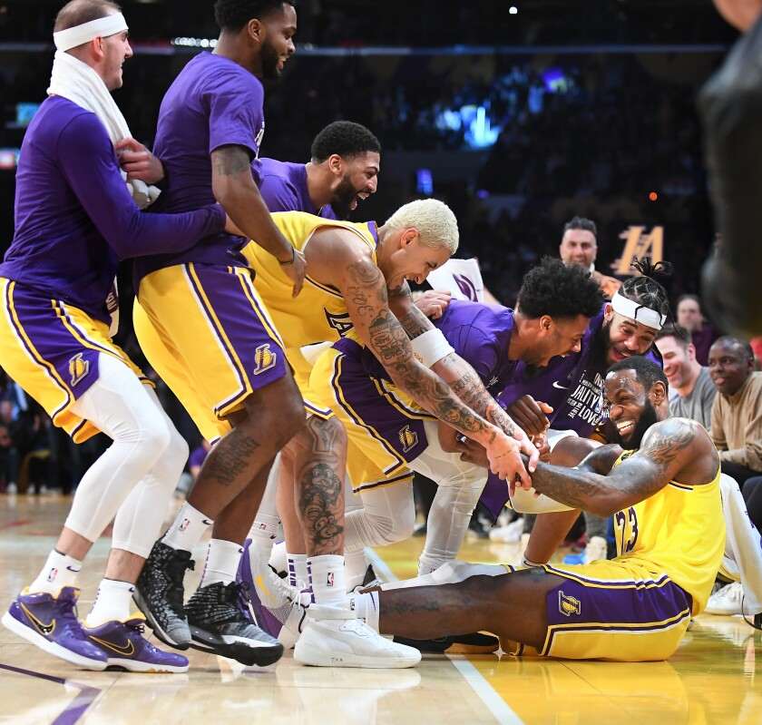 LeBron James is mobbed by his Lakers teammates after hitting a three-pointer against the Spurs on Feb. 4 at Staples Center.