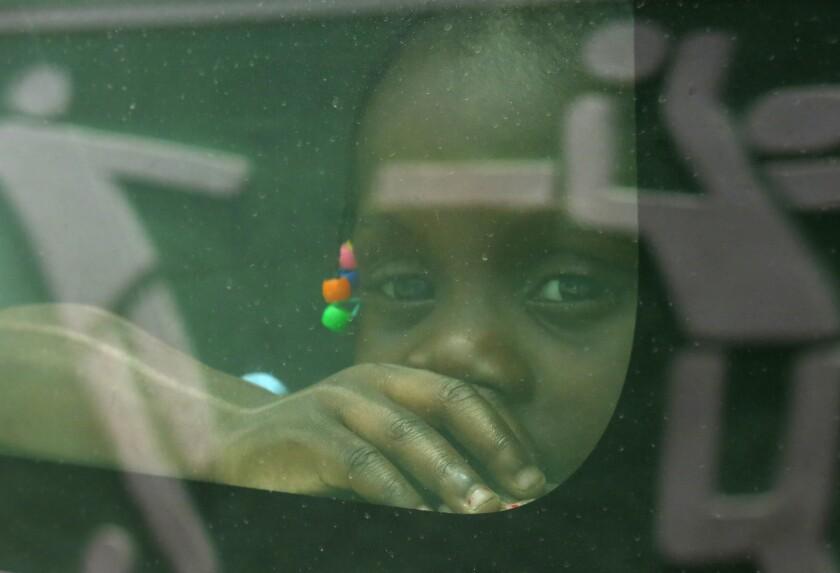 Una niña nacida en República Dominicana de padres haitianos mira a través de la ventana de un vehículo del gobierno mientras es trasladada junto a su familia a la frontera con Haití, en Santo Domingo.