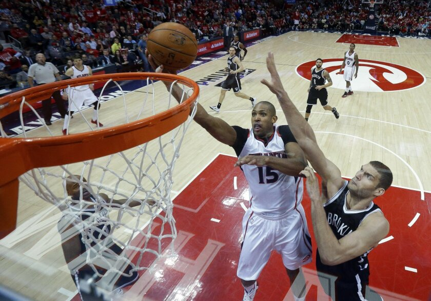 Atlanta Hawks center Al Horford (15) goes up for a basket as Brooklyn Nets center Brook Lopez (11) defends second half of Game 5 of a first round NBA playoff basketball game Wednesday, April 29, 2015, in Atlanta. Atlanta won 107-97 and leads 3 games to 2. (AP Photo/John Bazemore)