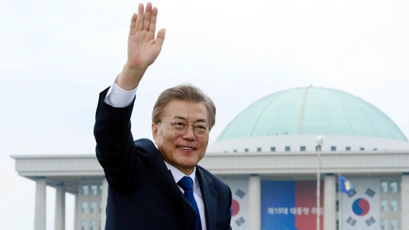 South Korea's new president, Moon Jae-in, waves from a car after his inauguration ceremony outside of the National Assembly in Seoul on May 10.