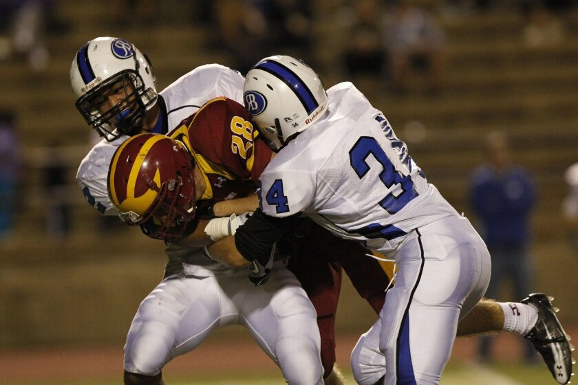 Torrey Pines #28 Mitchell Yocom is tackled by Rancho Bernardo players last month. His mother says pressure to pay for sports this season was lessened, with payments portrayed more as donations than requirements.