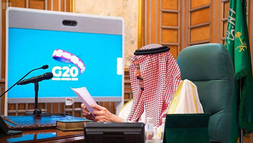 Saudi King Salman sits at a desk holding papers while having a video call with the Group of 20 logo behind him.