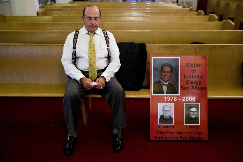 Arthur Baselice, the father of Arthur Baselice III, pictured in poster, sits on a pew after a news conference in Philadelphia last week. Baselice said his son was abused by a priest and a religious brother, became addicted to drugs and killed himself. Baselice said the Vatican needs to find ways to hold church leaders accountable for sheltering predators.