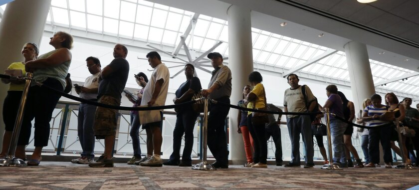 FILE - In this Sept. 3, 2014 photo, people wait in line to sign up for unemployment in Atlantic City, N.J. Payroll processor ADP reports how many jobs private employers added in September on Wednesday, Oct. 1, 2014. (AP Photo/Mel Evans, File)