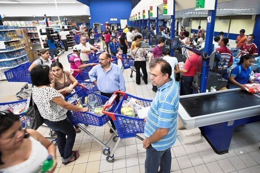 Shoppers stock up on supermarket items in Puerto Ordaz, Venezuela, the day before the presidential election.