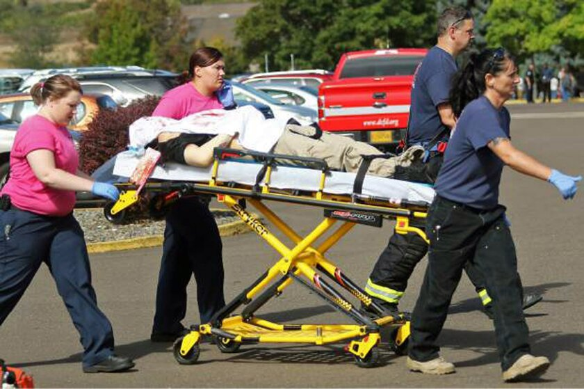 Authorities carry a shooting victim away from the scene after a gunman opened fire Thursday at Umpqua Community College in Roseburg, Ore. Yes, yet another mass shooting in America.