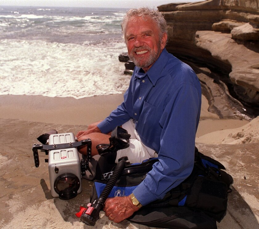 In this file photo from 2000, diver and photographer Chuck Nicklin poses with the tools of his trade on a beach near his home in La Jolla.