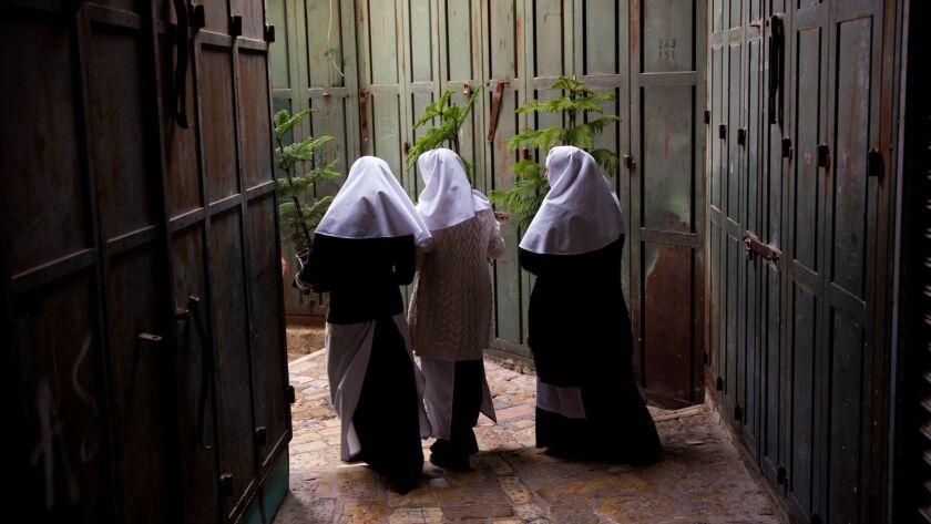 Christian nuns carry Christmas trees in Jerusalem Old City, Thursday, Dec. 21, 2017. The Jerusalem M