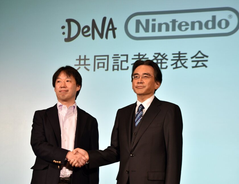 Japan's video game giant Nintendo President Satoru Iwata, right, with Japanese online game operator DeNA President Isao Moriyasu during a press conference in Tokyo on March 17, 2015.