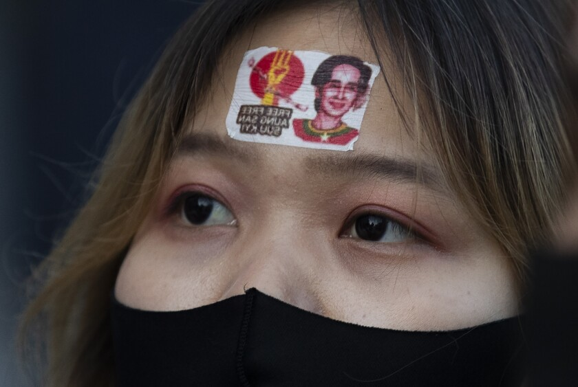 """A supporter of a protest group called """"WeLoveMyanmar"""" wears a sticker with an image of Myanmar leader Aung San Suu Kyi as they gather for a protest against the Myanmar military in front of the United Nations University in Tokyo on Thursday, Feb. 11, 2021. (AP Photo/Hiro Komae)"""
