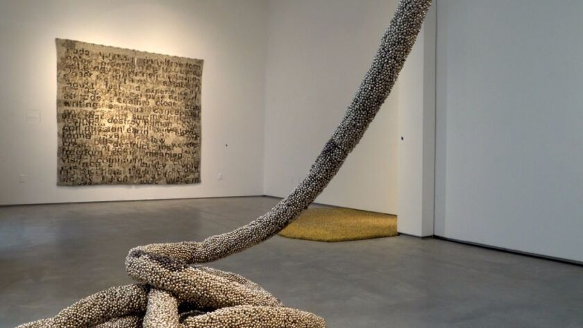 """Works by Vibha Galhotra: on wall, """"World Trash,"""" and in foreground, """"Between."""""""