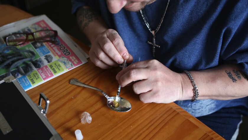 A heroin user prepares to shoot up in New London, Conn., an area hit hard by the surging heroin problem.