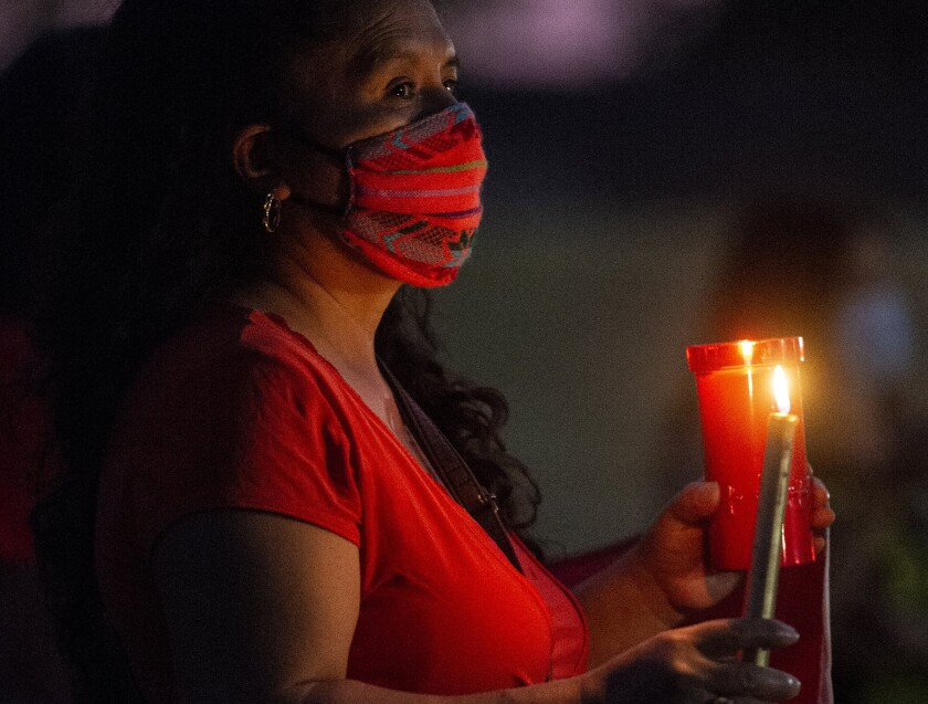 A woman holds a candle at a September vigil for workers at a Foster Farms plant in Livingston, Calif., who died of COVID-19