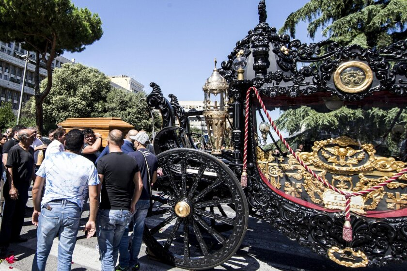 """Pallbearers carry the coffin of Vittorio Casamonica, identified by officials as one of the bosses of the Casamonica clan, next to a horse-drawn carriage, during the funeral ceremony in Rome, Thursday, Aug. 20, 2015.Romans aghast at a spiraling mafia probe have found new reason for alarm with the Hollywood-style funeral of a purported crime boss, replete with gilded horse-drawn carriage, flower petals tossed from a helicopter and the theme music from """"The Godfather."""" (Massimo Percossi/ANSA via AP)"""