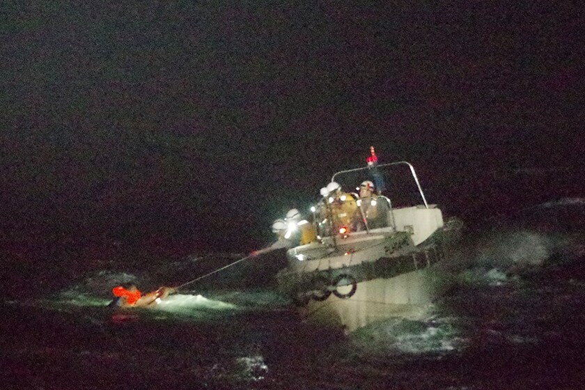 A crewman of a Panamanian cargo ship is rescued by Japanese Coast Guard members Wednesday.