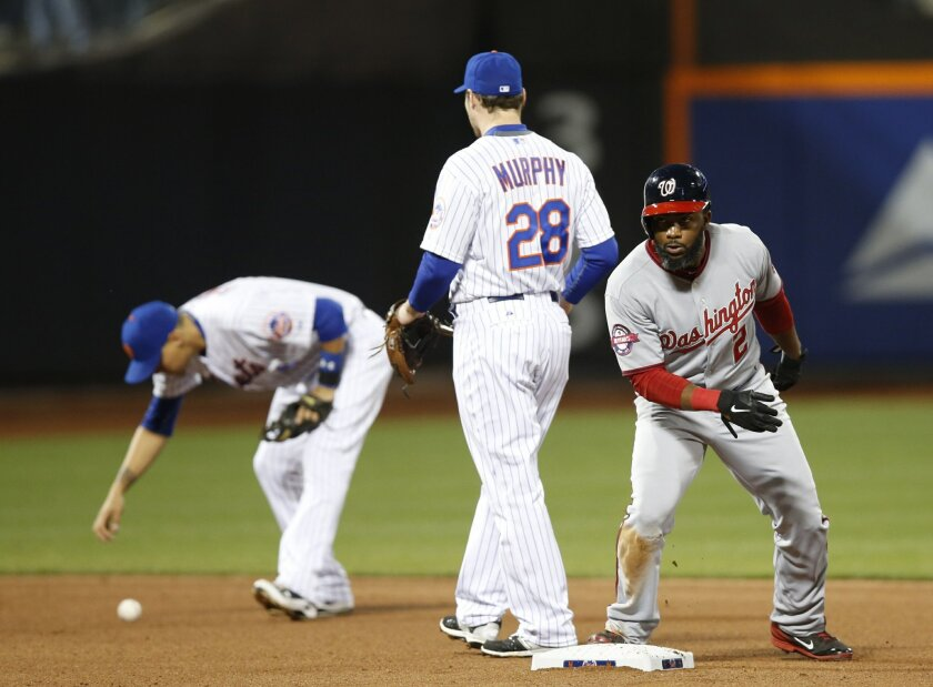 New York Mets second baseman Daniel Murphy (28) watches as Washington Nationals Denard Span (2) pulls into second on a Wilmer Flores's fourth-inning fielding error in a baseball game in New York, Thursday, April 30, 2015. Flores is shown picking up the ball, left, after the error. (AP Photo/Kathy W