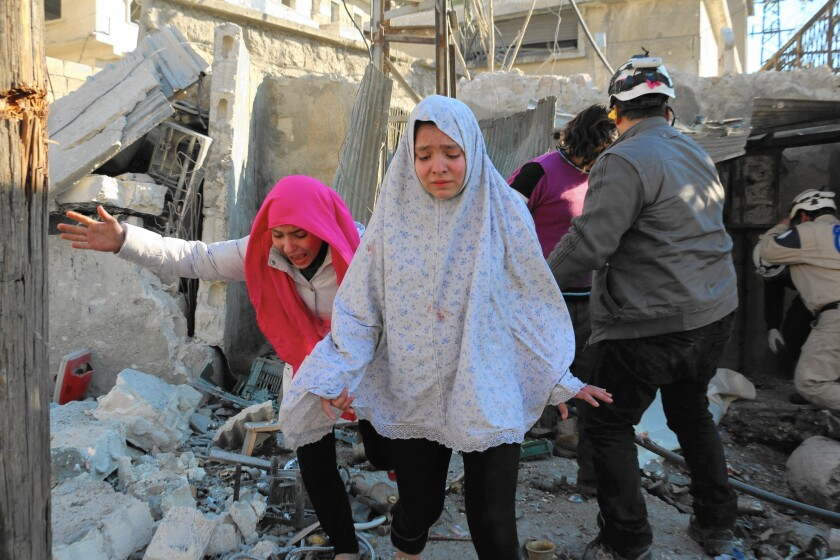 Girls make their way through a rebel-controlled neighborhood in Aleppo after an airstrike on Feb. 8.
