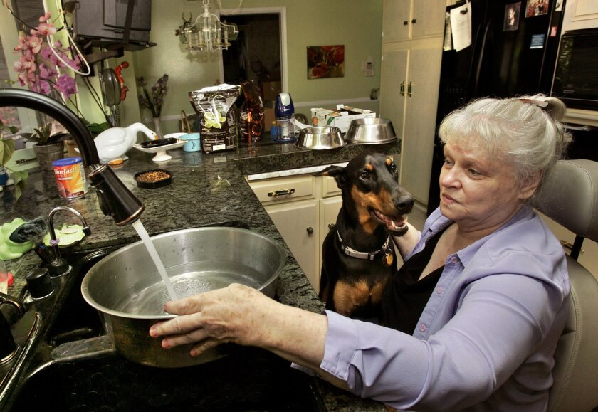 """Joyce Brown gets some water in her kitchen for her service dog named """"Mr. Spock,"""" a large Doberman Pinscher that drinks a lot of water."""