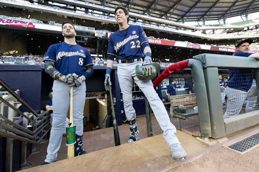 Ryan Braun (8) and Christian Yelich (22), who grew up in Southern California, stand in the dugout prior to a game against the Braves on May 18 at SunTrust Park.