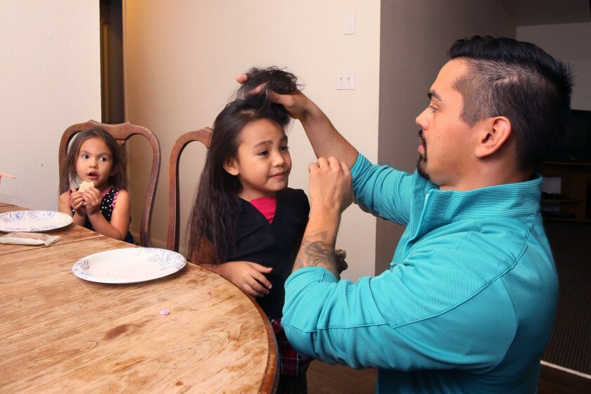 Single father Jared Hillaire works on the hair of his daughter Maya, 4, in their dining room. At left is daughter Jade, 3. They live at the Vista Terrace apartments that are owned by Solutions for Change.